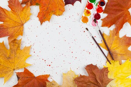 Palette of colors with brushes on gray with red spots background with autumn maple leaves top view, art workshop concept