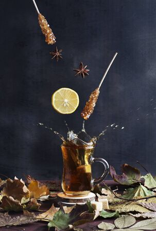 Magical tea concept. Levitating effect. Flying in air ingredients for tea, such as lemon, sugar on black background