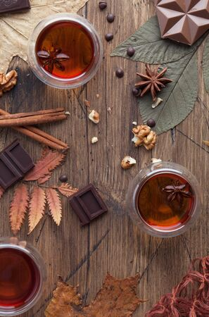 Flat lay autumn background. Cups of tea on rustic brown wooden table with chocolate, cinnamon, anise and leaves. Top view