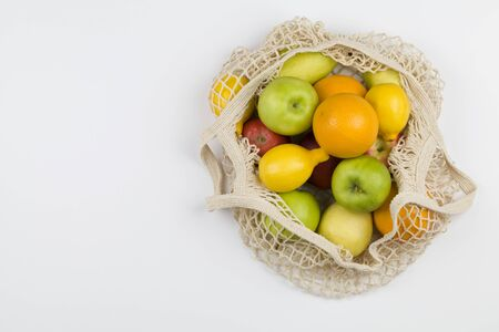 Mesh shopping bag with fruits apples, oranges, lemon and pears on white background. Top view, flat lay, copy space. Zero waste, eco friendly concept. Reklamní fotografie