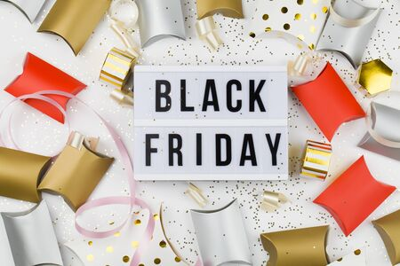Black friday sale text on white lightbox, golden stars, holiday ribbon and packaging around on white background. Template Black friday sale mockup fall thanksgiving promotion advertising Stok Fotoğraf