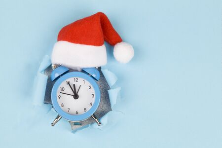 Alarm clock in red santas hat through hole in blue paper background. New Year background for presentation of work or text.greeting card. Copy space.Top view. Concept of lack of time, procrastination