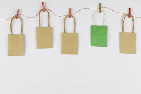 Colored packaging bags suspended on clothespins on white background. Banco de Imagens