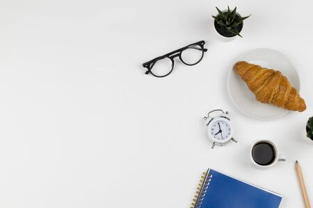 Businessman morning with blue notebook, cup of coffee, croissant , clock and glasses on white background top view mockup copy space flat lay