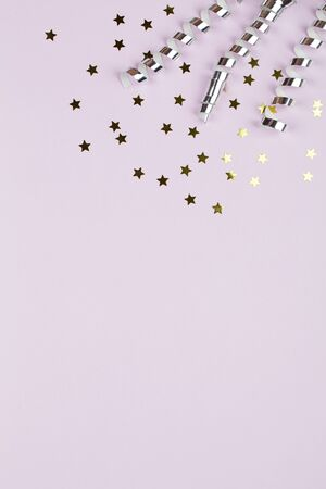Festive party border or frame of silver spiral streamers and confetti on pink background, copy space top view flat lay close up