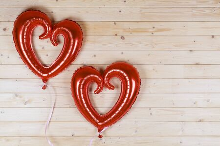 Big red heart balloons on wood background . Valentines day or birthday party background.