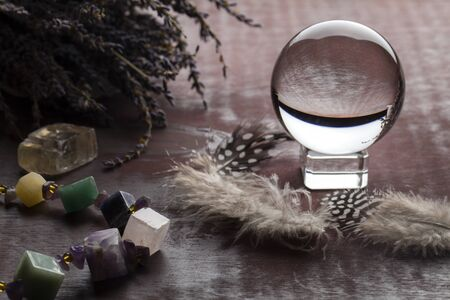 Divination with lavender, stones, feathers, fortune-telling ball. Halloween background, occult and esoteric objects on witch wooden table, Standard-Bild