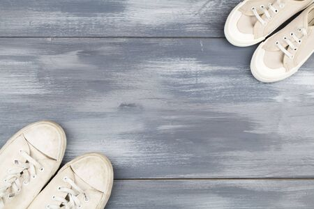 dirty white pair of sneakers opposite white baby sneakers on blue wooden background. concept of different generations . copy space Reklamní fotografie