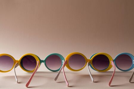 multi colored sunglasses with shadow as summer concept. Minimalist image of plastic sunglasses on brown background with copy space.