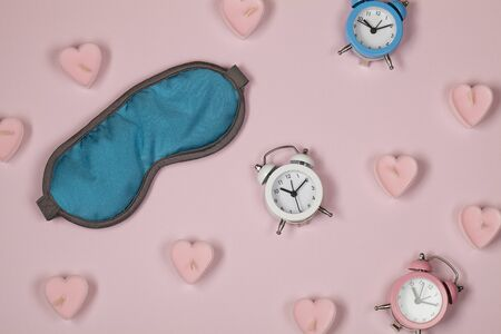 blue sleeping eye mask, alarm clocks and candles in form of hearts on pink pastel colourful background. Rest, good night, siesta, insomnia, relaxation, tired, travel concept.