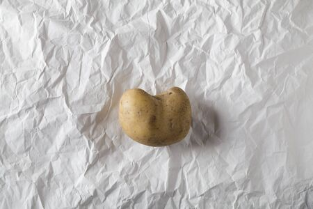 Ugly potato in the heart shape on crumpled craft white paper. unnormal vegetable environmental concept
