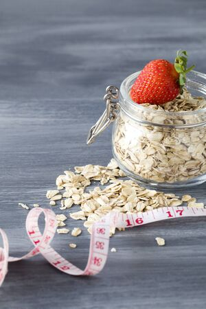 Natural oatmeal, measurement and strawberry on blue wood background . Oatmeal in a glass pot. Healthy breakfast concept . copy space Stok Fotoğraf - 147582400