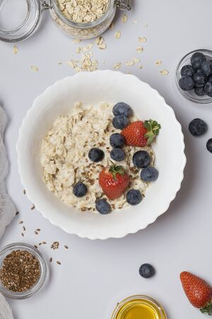 Oatmeal porridge with strawberry, blueberry, flax seeds and honey on gray background. Healthy breakfast for children and parents. vegetarian food. Stok Fotoğraf