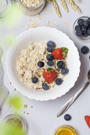 Oatmeal porridge with strawberry, blueberry, flax seeds and honey on gray background. Healthy breakfast for children and parents. vegetarian food. Stok Fotoğraf - 147583097