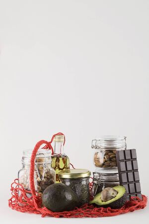 healthy fats sources flax nuts oil avocado chia seeds and bitter chocolate in red mesh bag .healthy food eco friendly concept, copy space