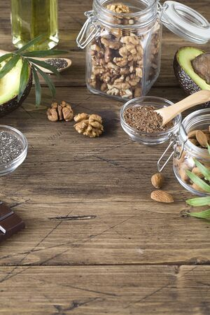 healthy fats sources flax nuts oil avocado chia seeds and bitter chocolate on brown wood background .healthy food eco friendly concept, copy space