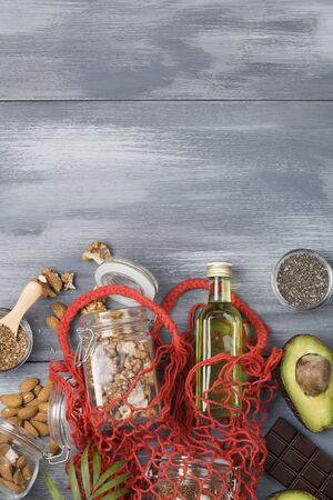 healthy fats sources flax nuts oil avocado chia seeds and bitter chocolate on blue wood background .healthy food eco friendly concept, copy space