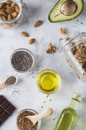 healthy fats sources flax nuts oil avocado chia seeds and bitter chocolate on blue background . healthy food concept,