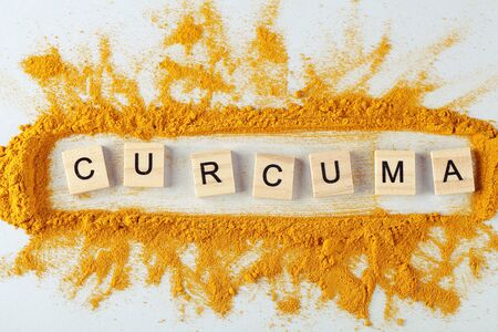 text curcuma and turmeric powder on gray background, indian spice, healthy seasoning ingredient for vegan cuisine