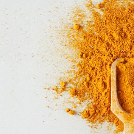 turmeric powder in wood spoon on gray background, indian spice, healthy seasoning ingredient for vegan cuisine copy space square
