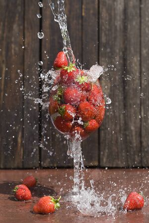 flow of water directed into glass with organic red strawberries on brown wood background. summer concept