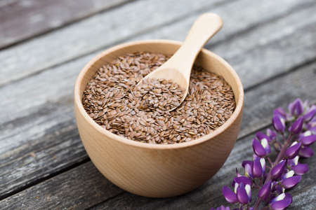 flax seeds in bowl and spoon on dark wooden background with flower lupine. Organic food concept. selective focus