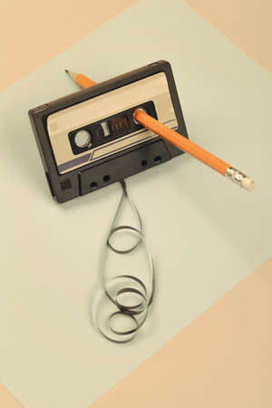 audio cassette with tangled tape on blue and beige background with yellow pencil, minimalistic composition. retro concept Banque d'images