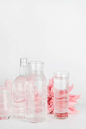 pink flowers distorted through water in glasses and bottle on white background. Home decor, eco friendly, relax, gardening concept. copy space
