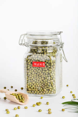mung in glass jar with wooden spoon on white background. healthcare lifestyle and organic food concept.