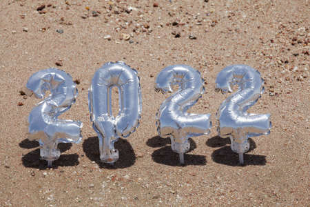 Christmas and happy new year concept. silver balloons in the form of numbers 2022 on the sand background with deep shadow.