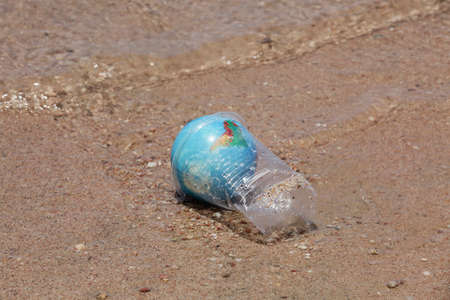 concept of environmental pollution. Planet Earth in plastic cup on the beach near sea. copy space. worldwide crisis of plastic pollution.