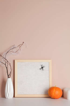 felt letter board with space for text with candle, pumpkin and branches on beige background.halloween day composition.party greeting card. Stock fotó