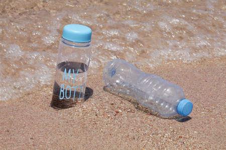 reusable water bottle against plastic bottle on beach near sea. reduce the plastic, zero waste concept. Stock fotó