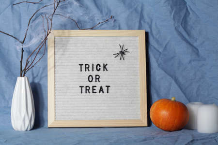 felt letter board with phrase trick and treat with candle, pumpkin on crumpled blue textile material.halloween day composition.party greeting card.