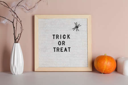 felt letter board with phrase trick or treat with candle, pumpkin and branches on beige background.halloween day composition.party greeting card. Stock fotó