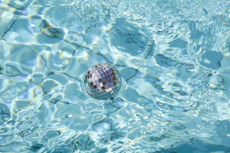 silver disco ball floating in blue water in pool. Christmas and happy new year concept.