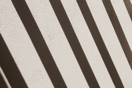 Gray wall with bright dark stripes from the sun. Minimal nature and abstract background. Stock fotó