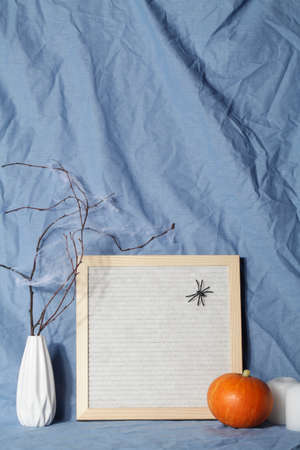 felt letter board with space for text with candle, pumpkin on crumpled blue textile material.halloween day composition.party greeting card.