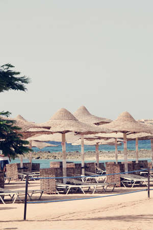 Beautiful beach. sun beds and umbrellas on the sandy beach by the sea. Summer holidays and the concept of recreation for tourism. tropical landscape