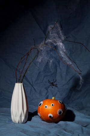 halloween day composition.party greeting card.pumpkin with eyes and dry branch with spider web on dark blue background.Creative halloween concept