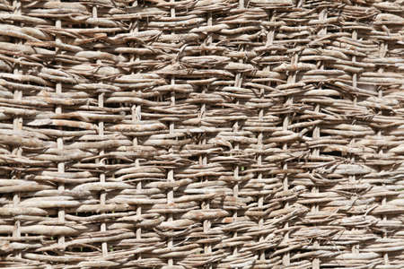 Weaving from branches. Background for the design of natural components. Handwork. Use of natural resources. Fence from tree branches.