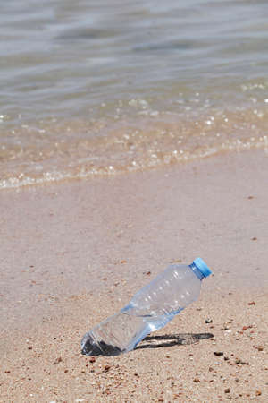 concept of environmental pollution. plastic bottle on the beach near sea. copy space. worldwide crisis of plastic pollution. Stock fotó