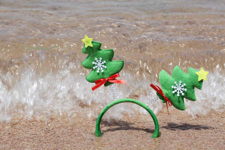 Christmas and happy new year concept. Headband with Christmas trees on the sand background near sea.