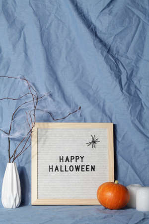 felt letter board with phrase happy halloween with candle, pumpkin on crumpled blue textile material.halloween day composition.party greeting card.