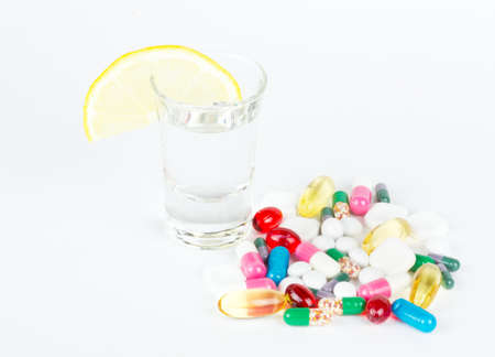 intoxicate: alcohol and tablets on white