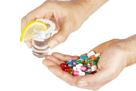 alcohol and tablets in hands on white