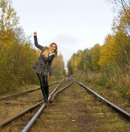 Young woman walking near railway Stock Photo