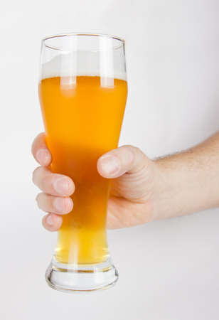 unfiltered: A glass of unfiltered beer in hand on white Stock Photo