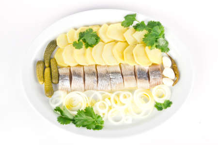 Plate with portion of herring fish fillets with potato and onion photo