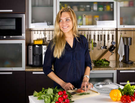Young blond woman making salad with fish in kitchen photo